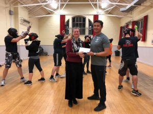 Catherine Batt, Finance Director at Smile Together CiC hands sponsorship cheque to Daniel Tswei, founder of Krav Maga Cornwall, Self Defence School.